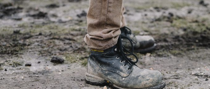 a person wearing dirty work boots